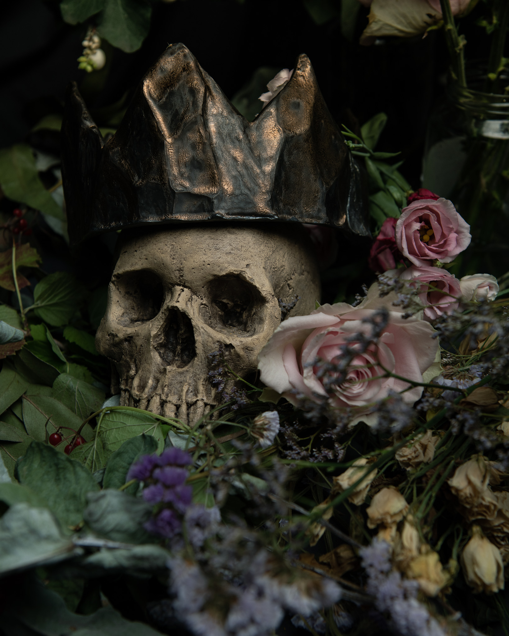 Arrangement of flowers, crown and skull
